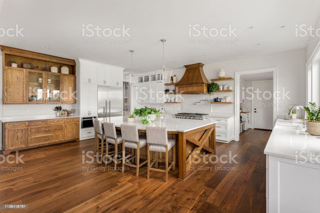 mooie keuken in nieuwe luxe huis met eiland, hanglampen, en hardhouten vloeren. - Royalty-free Aanrecht Stockfoto