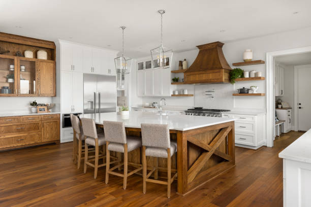beautiful kitchen in new luxury home with island, pendant lights, and hardwood floors. stock photo