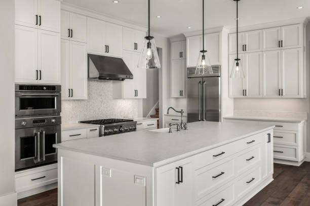 섬, 펜던트 조명 및 나무 바닥이있는 새로운 고급 주택의 아름다운 주방. 이중 오븐, 냉장고, 가스 레인지 및 후드를 포함한 스테인레스 스틸 가전 제품이 특징입니다. - 모던 양식 뉴스 사진 이미지