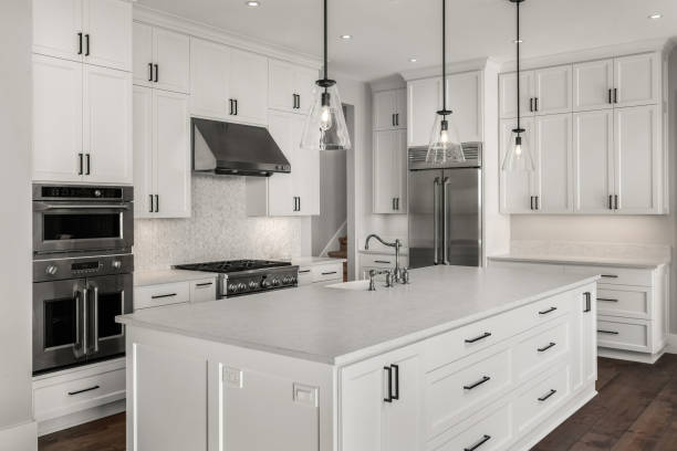 Beautiful kitchen in new luxury home with island, pendant lights, and hardwood floors. Features stainless steel appliances, including double oven, refrigerator, gas range and hood. stock photo