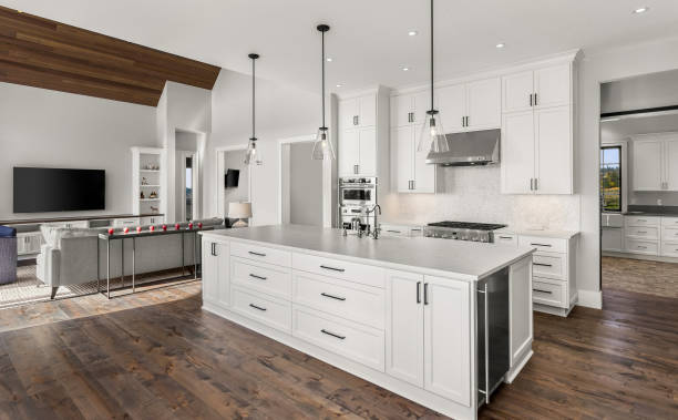 Beautiful kitchen in new luxury home with island, pendant lights, and hardwood floors. Features view of living room with vaulted ceiling. stock photo