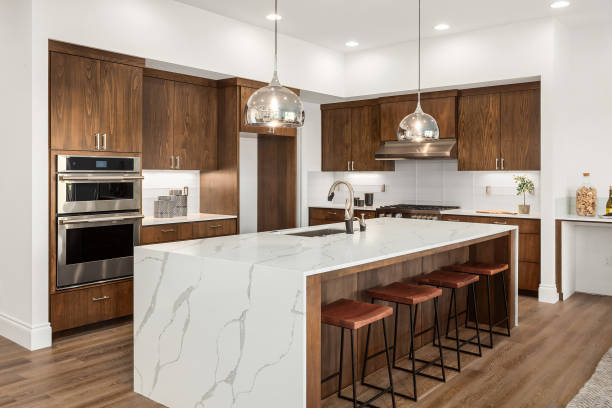 Beautiful kitchen in new luxury home with island, pendant lights, and hardwood floors. Features quartz waterfall island with dark cabinets and stainless steel appliances. stock photo