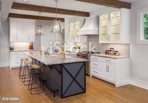 676153162 istock photo beautiful kitchen in new luxury home with island, pendant lights, and glass fronted cabinets 676153054