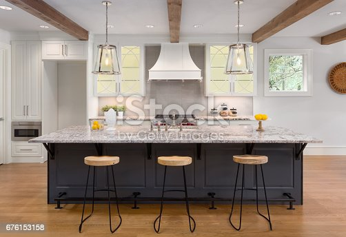 676153162 istock photo beautiful kitchen in new luxury home with island, pendant lights, and glass fronted cabinets 676153158