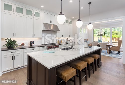 istock beautiful kitchen in new luxury home with island, pendant lights, and hardwood floors. Includes view of dining room. 692601402