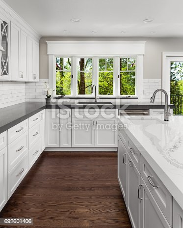676153162 istock photo beautiful kitchen in new luxury home with island, pendant lights, and hardwood floors. Includes two sinks. 692601406