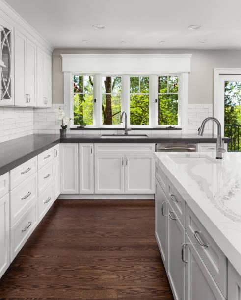 vackra kök i nya lyxhus med ön, hänge belysning och trägolv. innehåller två handfat. - looking inside inside cabinet bildbanksfoton och bilder