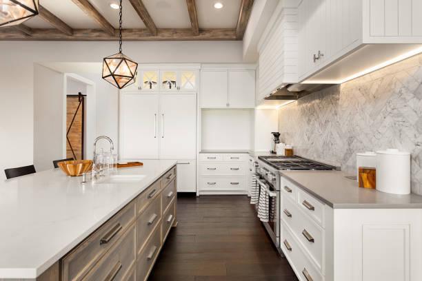 schöne küche im neuen luxus-haus mit insel, pendelleuchten und holzböden ausgestattet. - wohnschrank stock-fotos und bilder