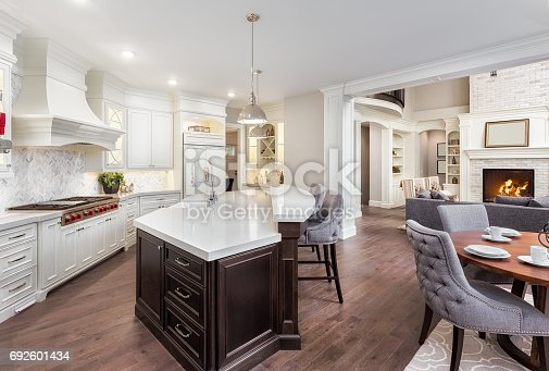 676153162 istock photo Beautiful kitchen in new luxury home with island, pendant lights, and hardwood floors. Includes view of dining room and living room with fire in fireplace 692601434