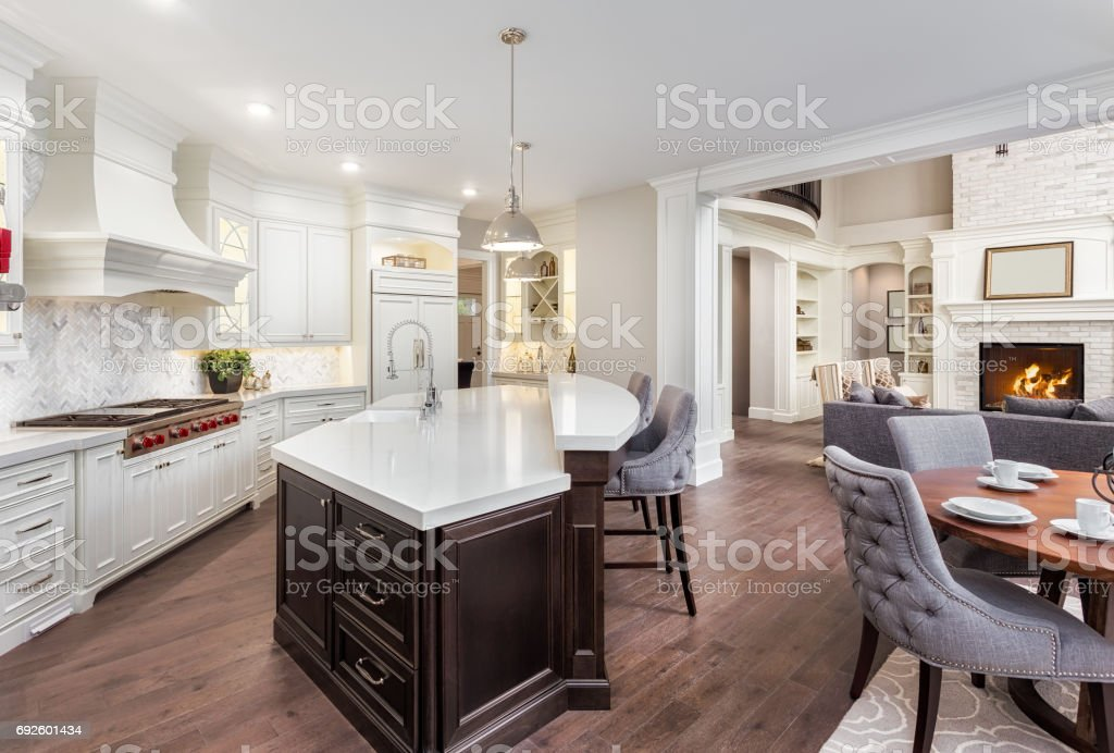 Beautiful kitchen in new luxury home with island, pendant lights, and hardwood floors. Includes view of dining room and living room with fire in fireplace stock photo