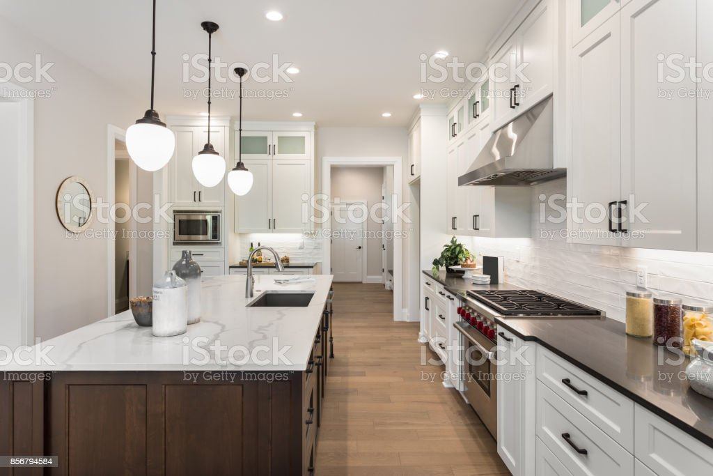 beautiful kitchen in new luxury home with island, pendant lights, and glass fronted cabinets royalty-free stock photo