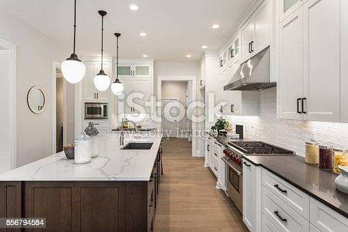 istock beautiful kitchen in new luxury home with island, pendant lights, and glass fronted cabinets 856794584