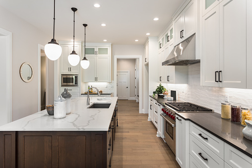 Beautiful Kitchen In New Luxury Home With Island Pendant Lights And Glass Fronted Cabinets Stock Photo - Download Image Now