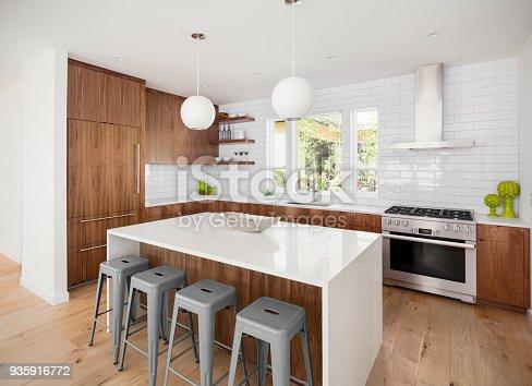 istock beautiful kitchen in new luxury home with island, pendant lights, and hardwood floors 935916772