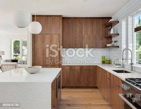 istock beautiful kitchen in new luxury home with island, pendant lights, and hardwood floors 935916780