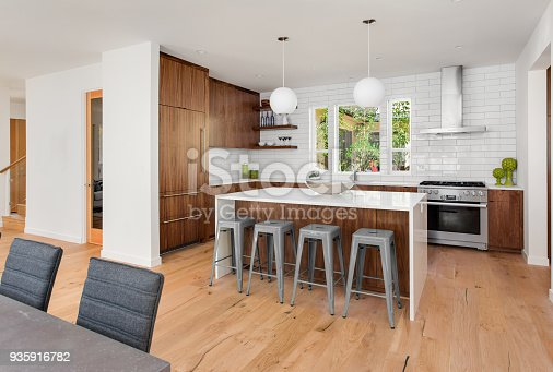 istock beautiful kitchen in new luxury home with island, pendant lights, and hardwood floors 935916782