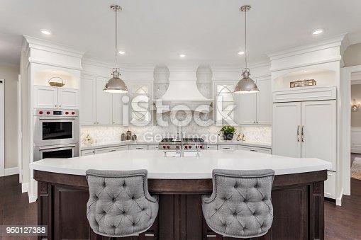 istock beautiful kitchen in new luxury home with island, pendant lights, and hardwood floors 950127388