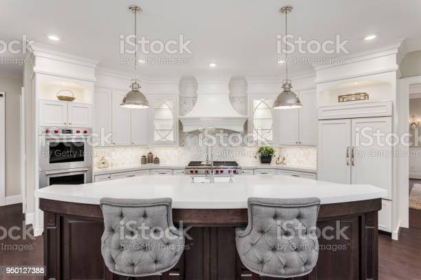 Beautiful kitchen in new luxury home with island pendant lights and picture id950127388?b=1&k=6&m=950127388&s=612x612&h=as65whtfd6iads9bkc8bxe lbhv7nwqajkkjornqacy=