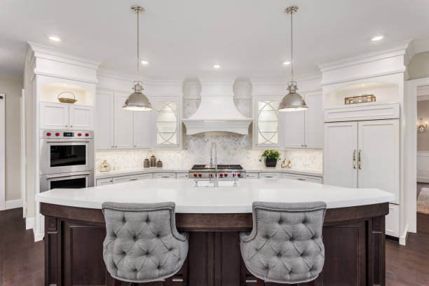 beautiful kitchen in new luxury home with island, pendant lights, and hardwood floors - kitchen situations foto e immagini stock