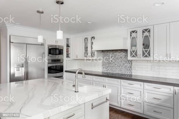 Beautiful kitchen in new luxury home with island pendant lights and picture id950127420?b=1&k=6&m=950127420&s=612x612&h=t7kvkujfz9x8j0507giozmx0iutzlfoxbi2eh6vxnzu=