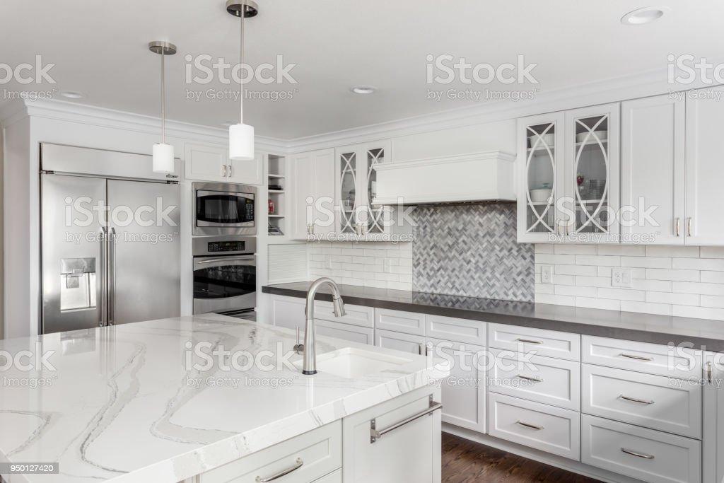 bela cozinha em casa com a ilha, pingente luzes e pisos de madeira de luxo nova - foto de acervo