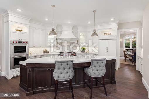 676153162 istock photo beautiful kitchen in new luxury home with island, pendant lights, and hardwood floors. Has partial view of dining room 950127434
