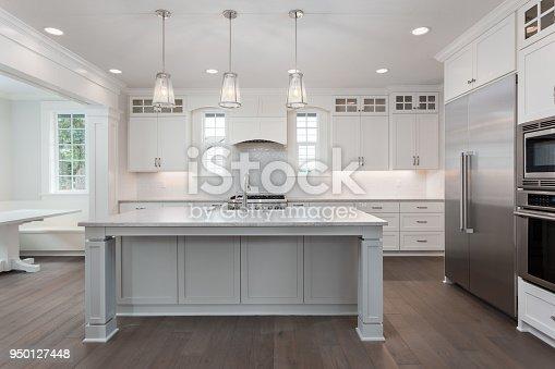 istock beautiful kitchen in new luxury home with island, pendant lights, and hardwood floors 950127448