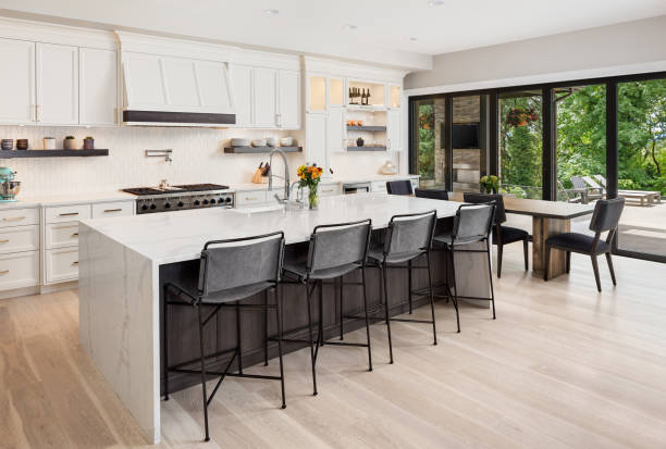 beautiful kitchen in new luxury home with island, pendant lights, oven, range, and hardwood floors. stock photo