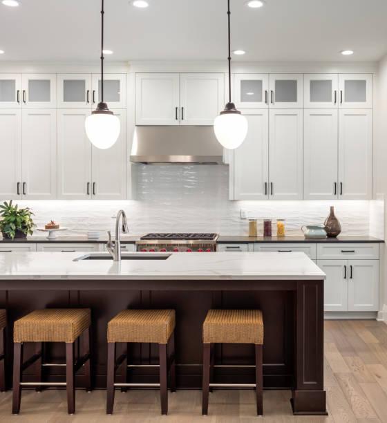 schöne küche im neuen luxus-haus mit insel, pendelleuchten, ofen, reichweite und holzböden ausgestattet. - wohnschrank stock-fotos und bilder