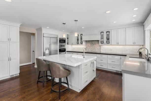 beautiful kitchen in new luxury home with island, pendant lights, oven, range, and hardwood floors.