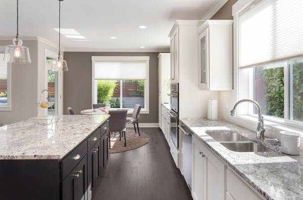 beautiful kitchen in new luxury home with island, pendant lights, oven, range, and hardwood floors. - kitchen situations foto e immagini stock