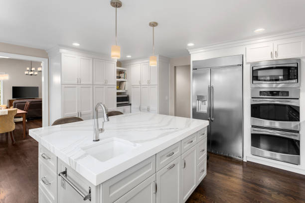 beautiful kitchen in new luxury home with island, pendant lights, stainless steel appliances, and hardwood floors kitchen in newly constructed luxury home quartz stock pictures, royalty-free photos & images