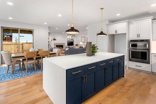 vackert kök i nytt lyxigt hem med stor ö, hängande lampor och trägolv. shower matsal och vardagsrum. - looking inside inside cabinet bildbanksfoton och bilder