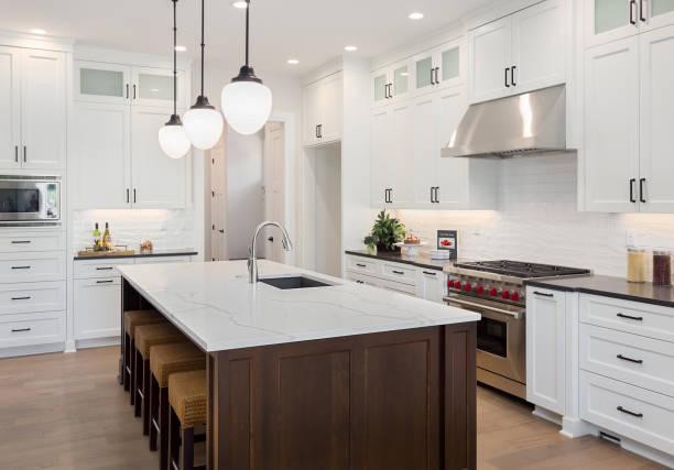 schöne küche im neuen luxus-haus mit großen insel, pendelleuchten, ofen, reichweite und holzböden ausgestattet. - wohnschrank stock-fotos und bilder