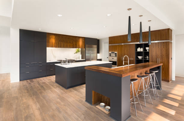 beautiful kitchen in new luxury home with two islands, two sinks, pendant lights, oven, range, and hardwood floors stock photo