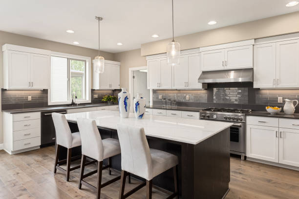 beautiful kitchen in new residential home with island, pendant lights, and hardwood floors.