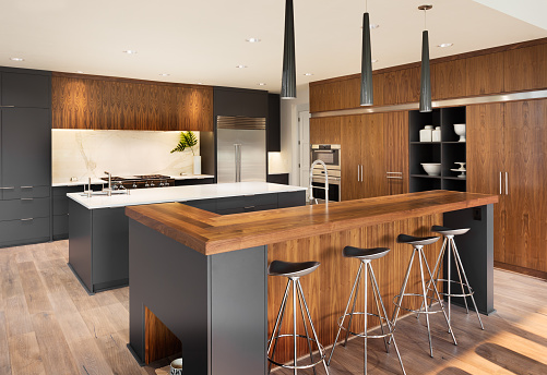 kitchen in luxury home with two islands, stainless stell appliances, and gorgeous hardwood cabinetry
