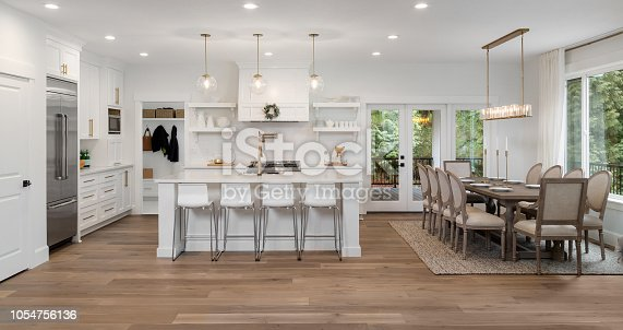 676153162 istock photo beautiful kitchen panorama in new luxury home with island, pendant lights, and hardwood floors. Also features dining room and dining room table 1054756136