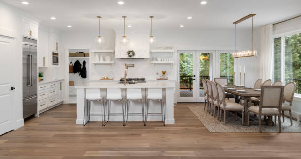 beautiful kitchen panorama in new luxury home with island, pendant lights, and hardwood floors. Also features dining room and dining room table stock photo