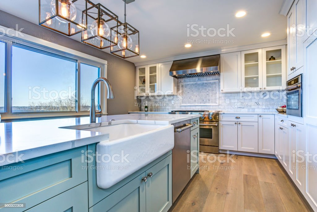 Beautiful kitchen room with green island and farm sink. stock photo