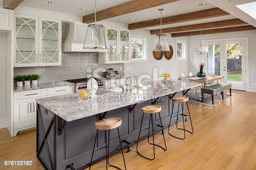 676153162 istock photo beautiful kitchen with lights off in new luxury home with island, pendant lights, and glass fronted cabinets, and view of dining room 676153162