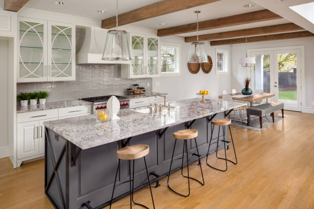 beautiful kitchen with lights off in new luxury home with island, pendant lights, and glass fronted cabinets, and view of dining room stock photo