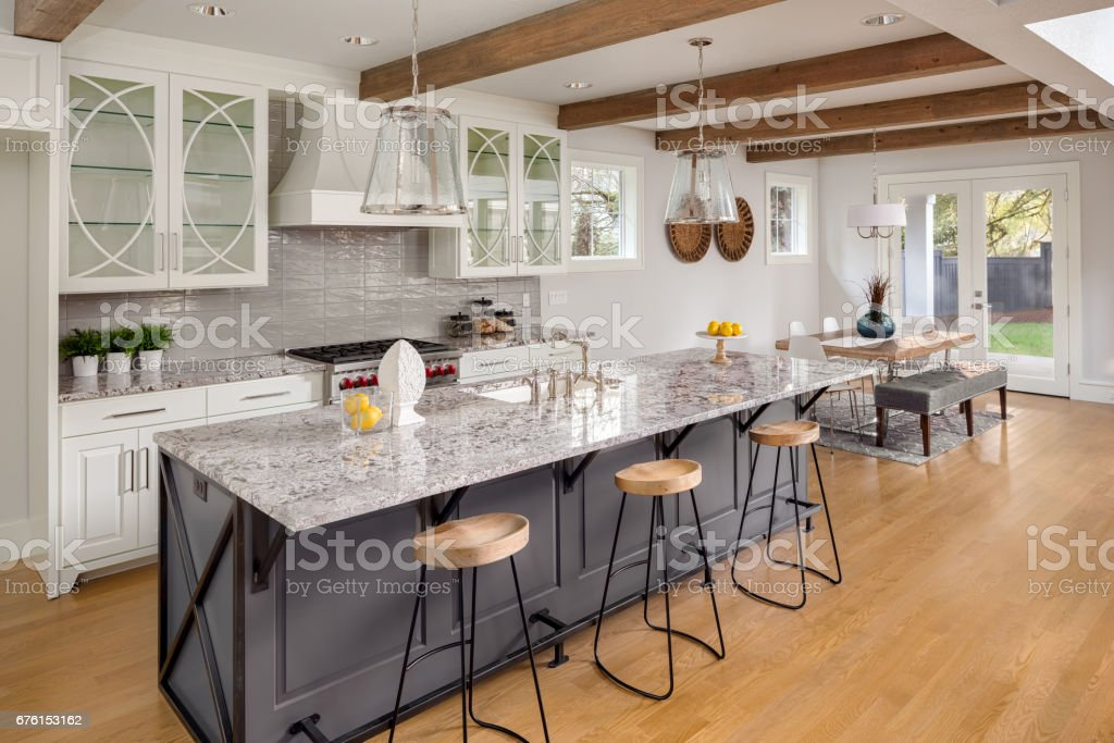beautiful kitchen with lights off in new luxury home with island, pendant lights, and glass fronted cabinets, and view of dining room – Foto