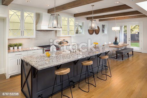 676153162 istock photo beautiful kitchen with lights on in new luxury home with island, pendant lights, and glass fronted cabinets, and view of dining room 676153208