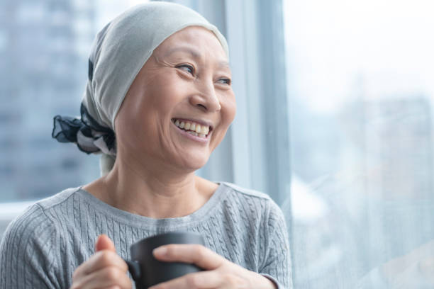 beautiful korean woman with cancer looks out window - cancer patient stock pictures, royalty-free photos & images