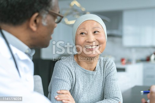 A Korean woman with cancer is meeting with her doctor. Chemotherapy treatment is going well. The patient is smiling at her doctor as he shares with her positive news.