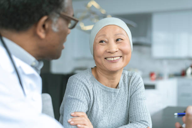 beautiful korean woman with cancer smiles at doctor - cancer patient stock pictures, royalty-free photos & images