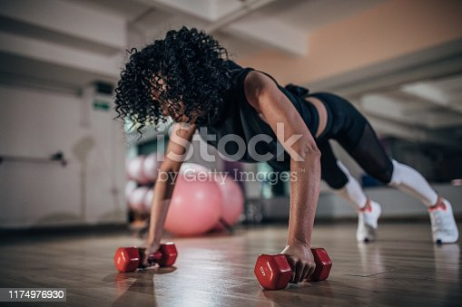 One woman, training alone with push-ups on dumbbells in gym.