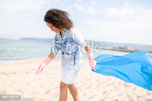 962184460 istock photo Beautiful lady during local clean up at the beach 962184756