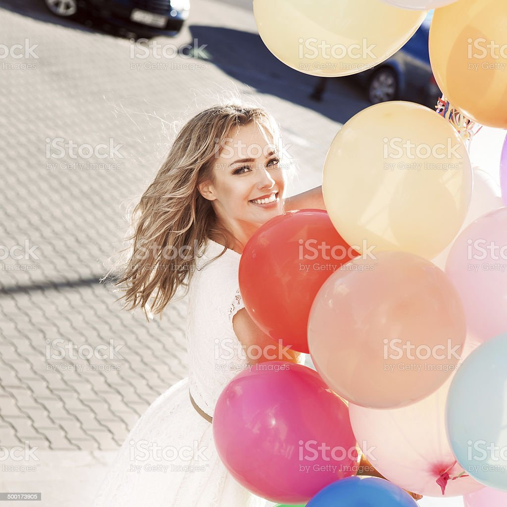 beautiful lady holding a bunch of balloons stock photo